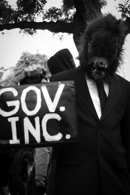A protester creatively makes a statement about the predatory nature of capitalism and the conflation of governments and corporations.