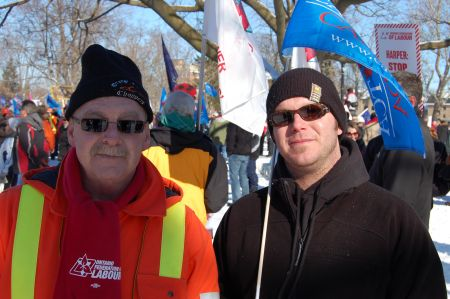 John Whitty (left) worked at the Electro-Motive Diesel (EMD) plant for 33 years. His son Chris (right) is now a maintenance electrician at EMD who has been locked out for over three weeks when workers rejected a proposed 50% wage cut. The Ontario Federation of Labour held a rally in Victoria Park in London, Ont. on Jan. 21  Photo: Mick Sweetman