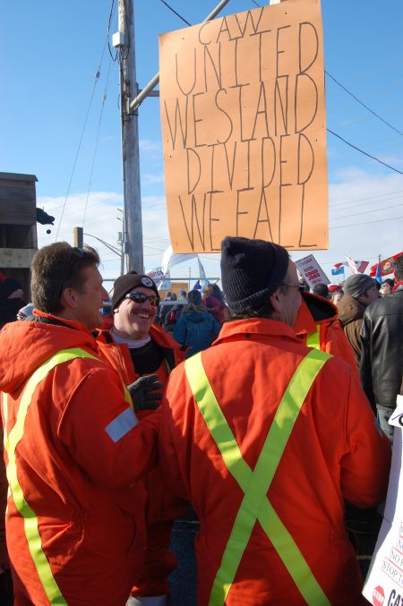 Locked out workers on the picket line share a laugh during a mass picket outside the Electro-Motive Diesel plant in London, Ont. on Jan. 21  Photo: Mick Sweetman