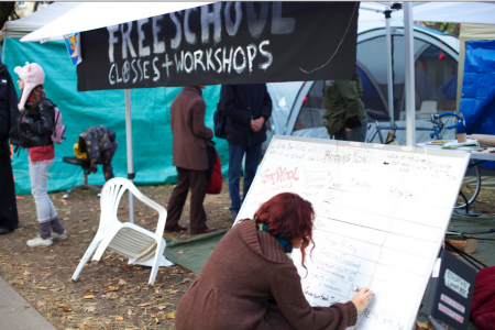 Rebecca, an occupy freeschool organizer, updates the whiteboard outside the Freeschool tent.