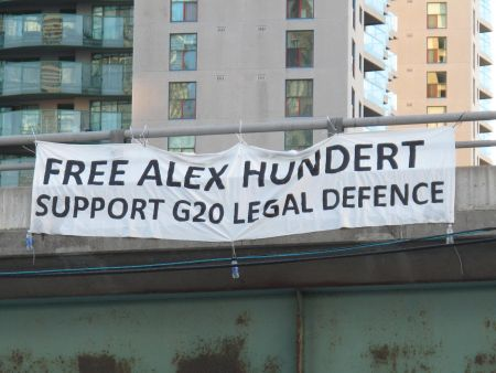 Environmental Justice Toronto activists drop banner off Gardiner Expressway  demanding freedom for G20 arrestee Alex Hundert