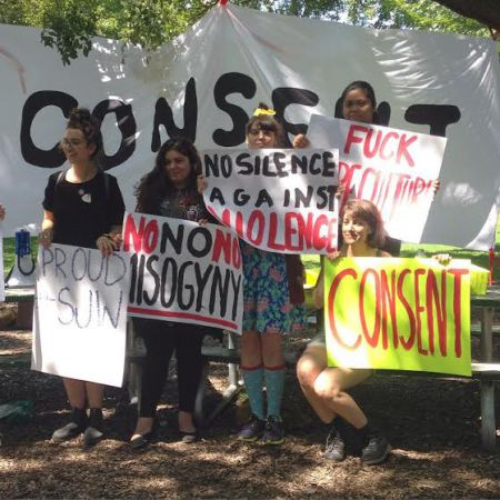 "Organizers stand in front of the large ""CONSENT"" banner. [Credit: Nyssa Komorowski]"