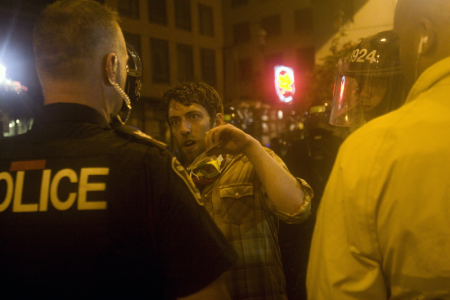 Rosenfeld shows his media credentials to police right before he is arrested and beaten. Photo: Activestills