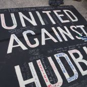 Attendees signed a banner in solidarity with communities across the Americas harmed by Hudbay Minerals. Photo by Kim Abis.