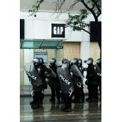 Police guard corporate storefronts going on 24 hours of sweeping mass arrests and street clashes
