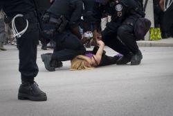 On voit une jeune dame blonde, portant une camisole et des leggings mauves, lancée au sol et se faire trainer par quelques agents antimeutes.