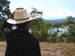 A mayan man looks on towards the tailings pond.  [Guatemala]