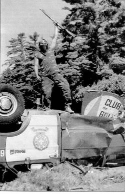 Warrior atop police vehicle, Kanehsatake / Oka Crisis 1990, photo by Tom Hanson, Canadian Press