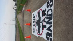 Stop the Tar Sands banner is laid out at the entrance to the site
