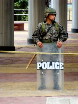 Nov. 27, 2009 - A few feet away, a military officer holds a riot shield that answers the question.