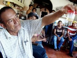 Nov. 29, 2009 - At a community meeting in Jutiapa, people give detailed accounts of the repression they have faced to members of FIAN human rights workers.  One man holds up a jar containing a piece of the skull of a local who was shot in the head by police a few months earlier.