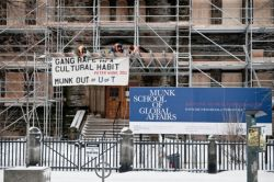 A banner dropped at the Munk School of Global Affairs